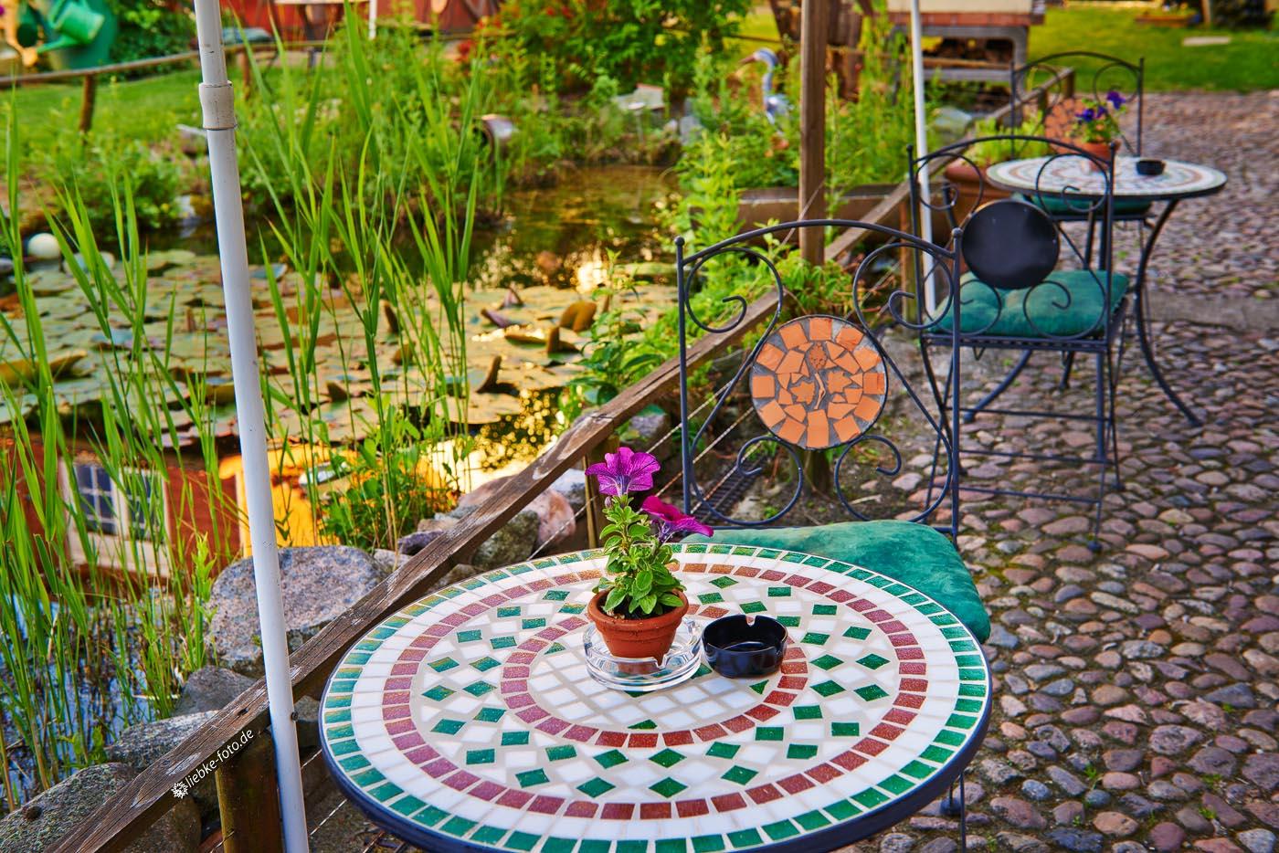 Entspanntes Sitzen am Teich im Hof der Weinschmiede Sommerfeld