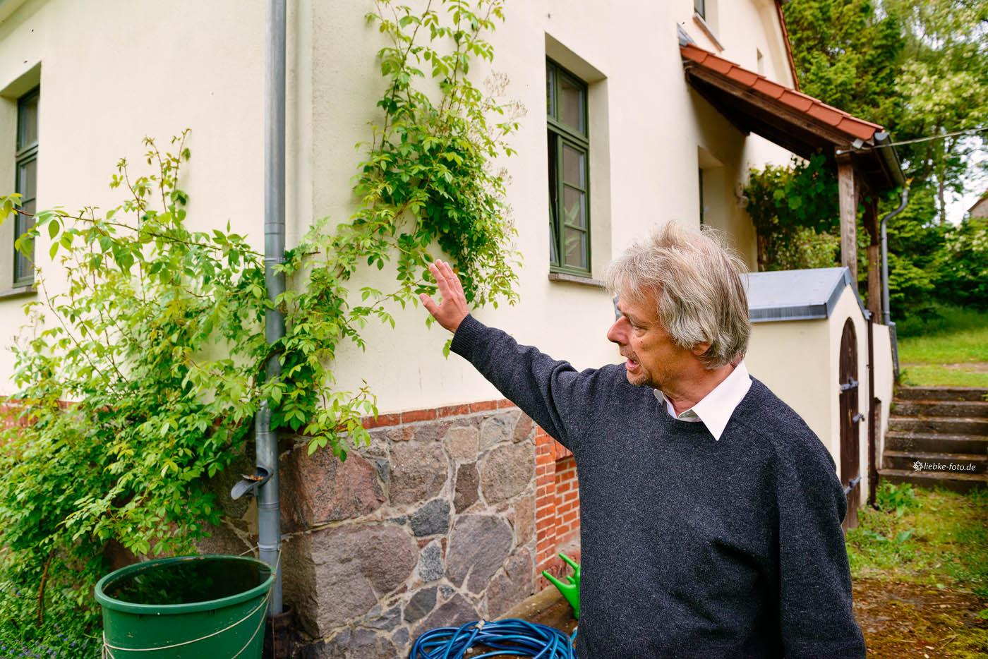 Pastor Ulrich Kasparick an der Kletterrose am Haus