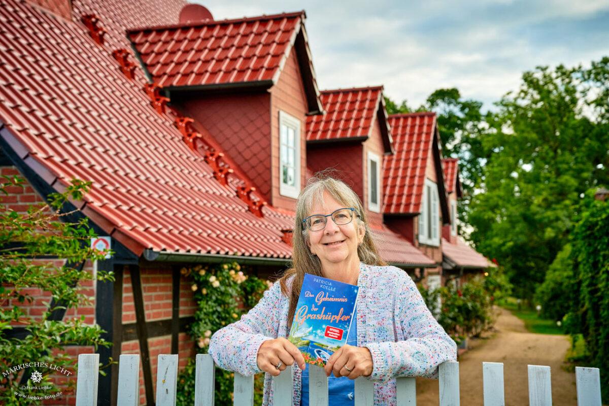 Lenzerwische, Patricia Koelle mit einem Vorexemplar ihres neuen Romans vor einem der Schauplätze, dem Landhaus Elbeflair.